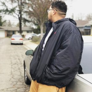 an image of MBKDeezy leaning on a car facing away from the camera.
